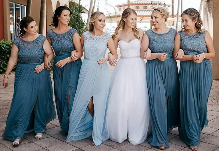 Bridesmaids in blue dresses linking arms with bride walking on a patio