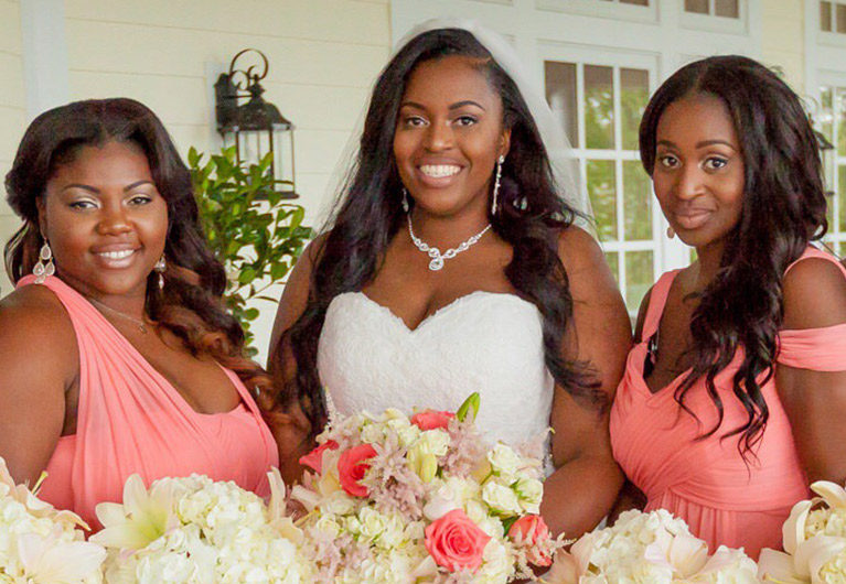 Bride smiling between two bridesmaids in pink dresses