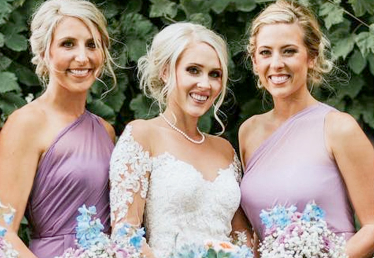 Bride smiling between two bridesmaids in purple dresses