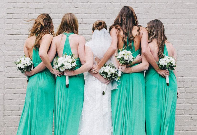 f2678d9d48a Bride and bridesmaids wrapping their arms around each other in a line from  the back with