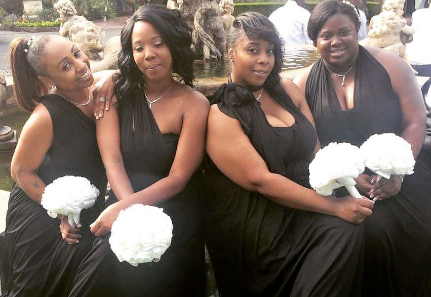 Four bridesmaids sitting by fountain with white bouquets wearing black dresses