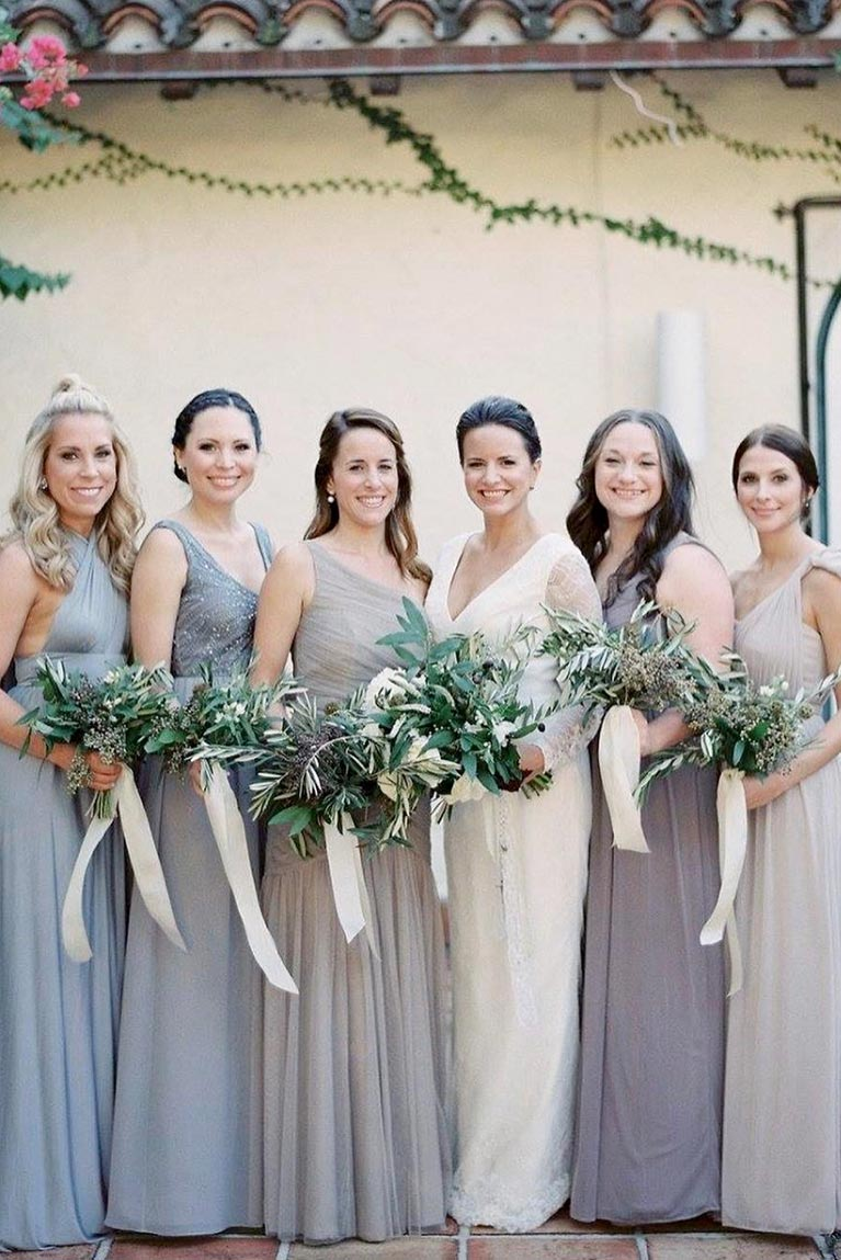 Bridesmaids standing closely together with greenery bouquets