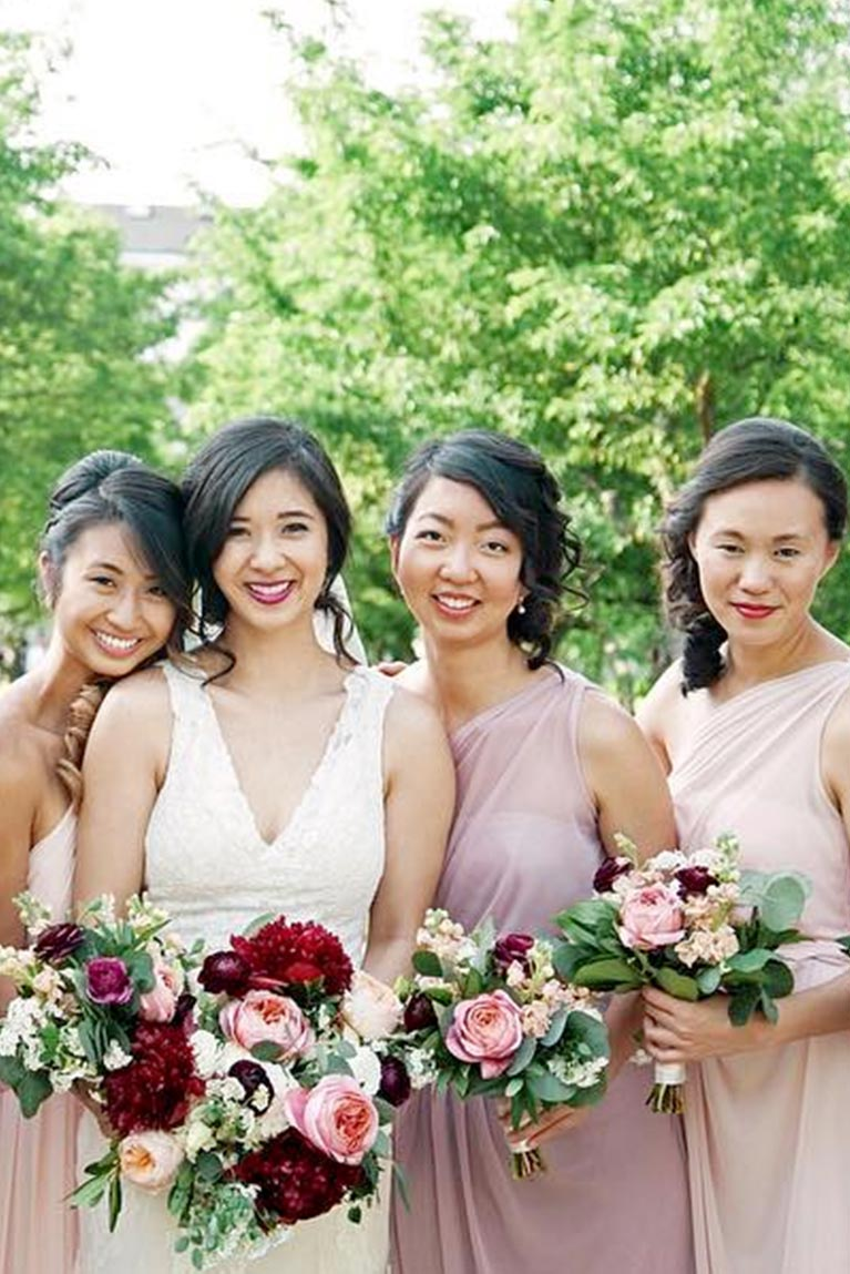 Bridesmaids posing closely with bride smiling