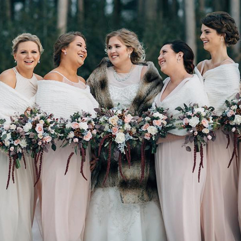 Bride and bridesmaids wearing faux fur shawls with wintery bouquets