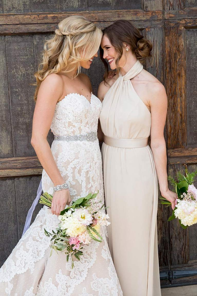 Bride and bridesmaid affectionately touching foreheads