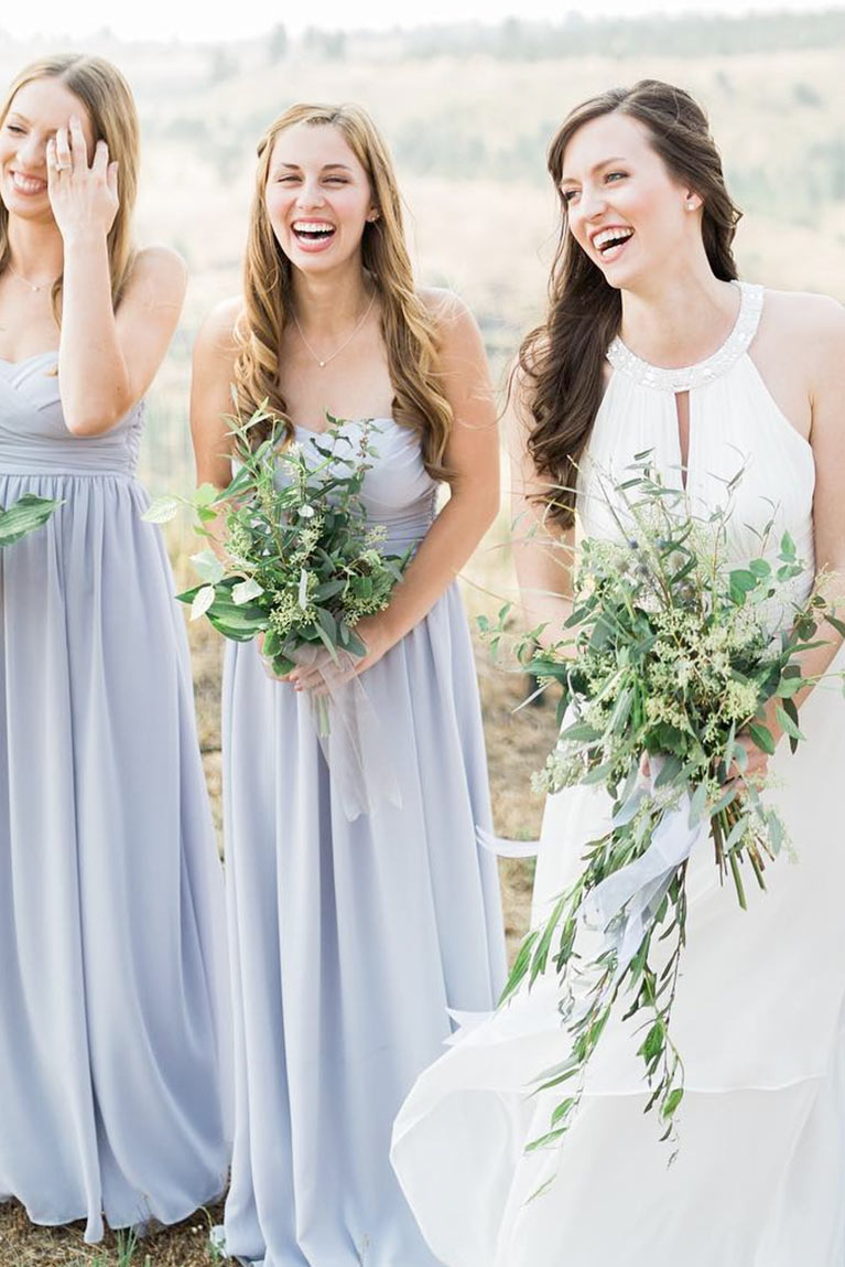 Bridesmaids laughing with bride holding greenery bouquets