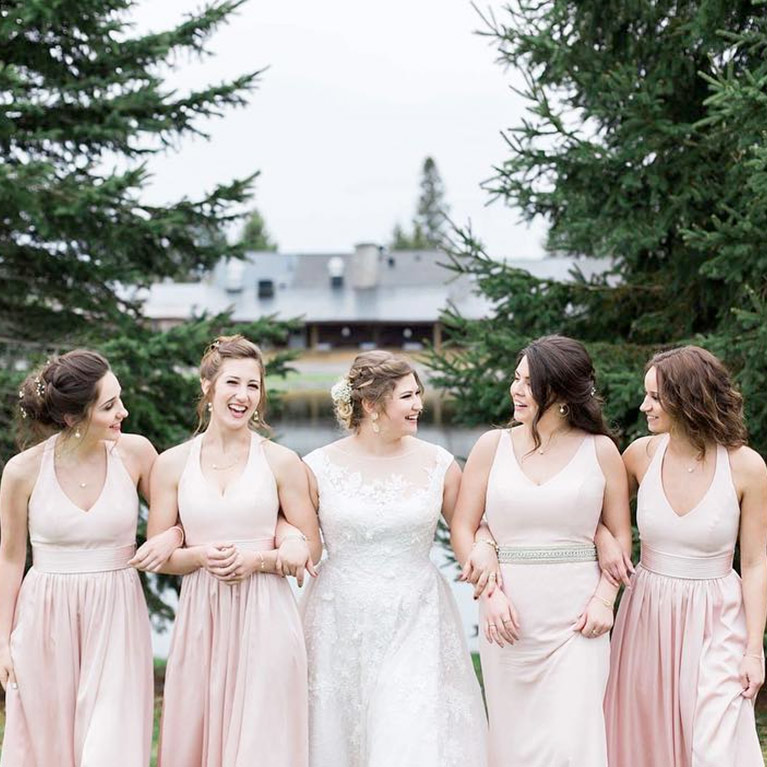 4446035415a Bridesmaids linking arms with brides in front of wooded resort