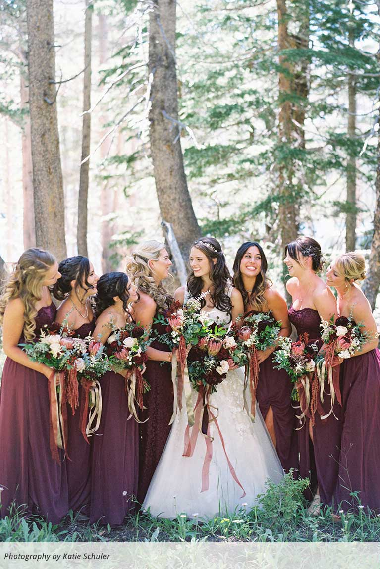 Bridesmaids with bride standing in wooded area with ribbon bouquets