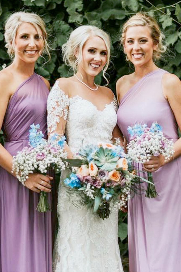 Bride and two bridesmaids standing closely together smiling by ivy backdrop