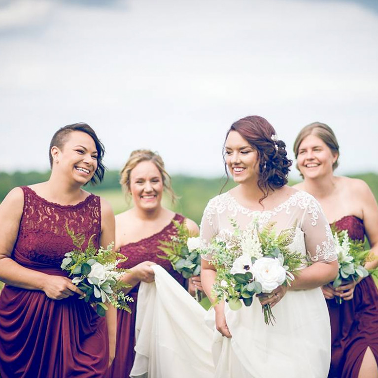 Bridesmaids helping bride carry her train through a meadow