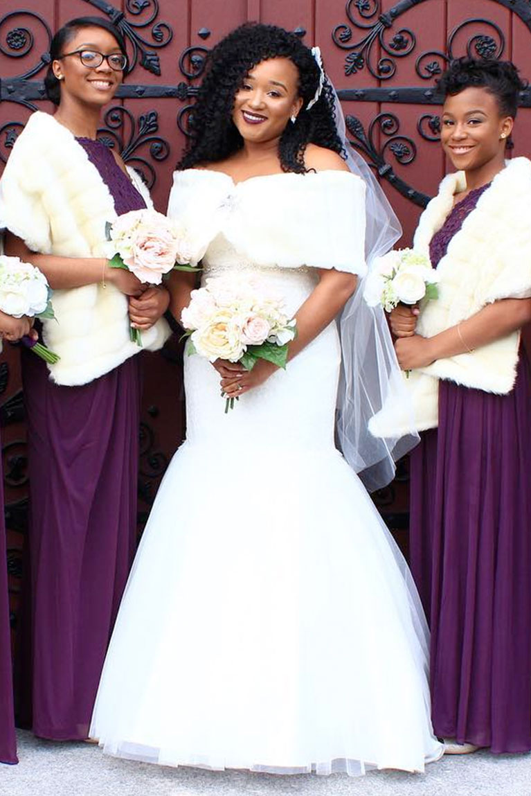 Bride and bridesmaids wearing white faux fur winter shawls in front of grand door