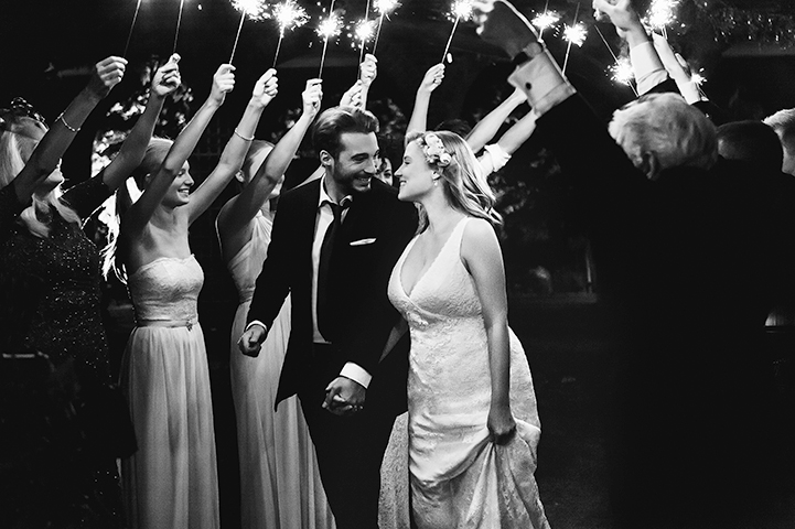 Couple in suit and wedding gown walking down aisle surrounded by people holding sparklers