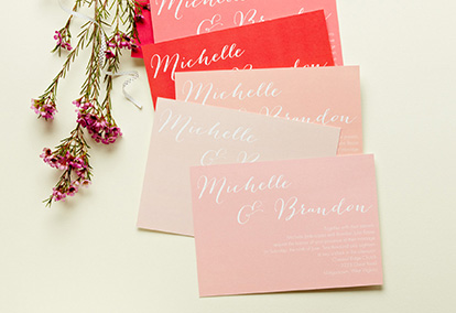 Pink and Coral Wedding Invitations Next to Flowers