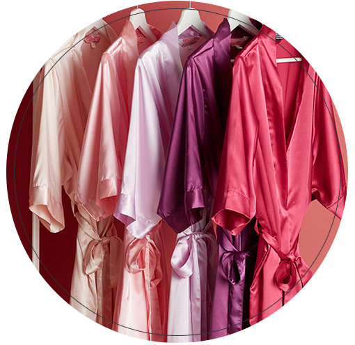 Robes in various shades of pink and purple hanging on rack