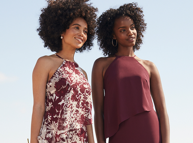 Two bridesmaids wearing wine colored dresses standing closely