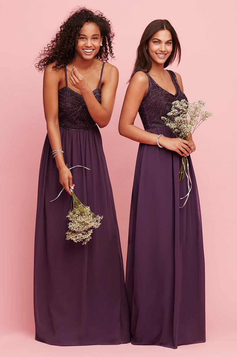 Two bridesmaids in plum dresses holding flowers