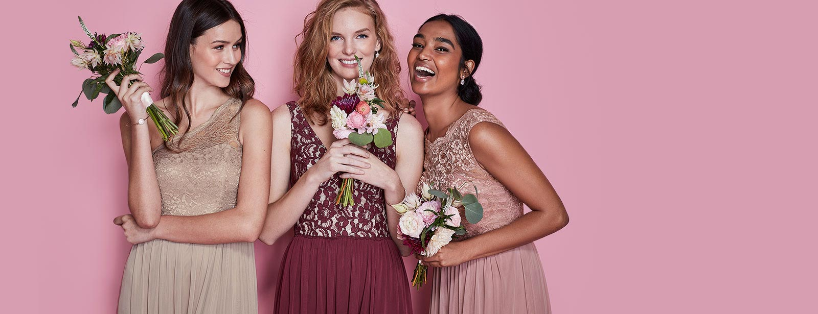 Three bridesmaids in colorful dresses holding flower