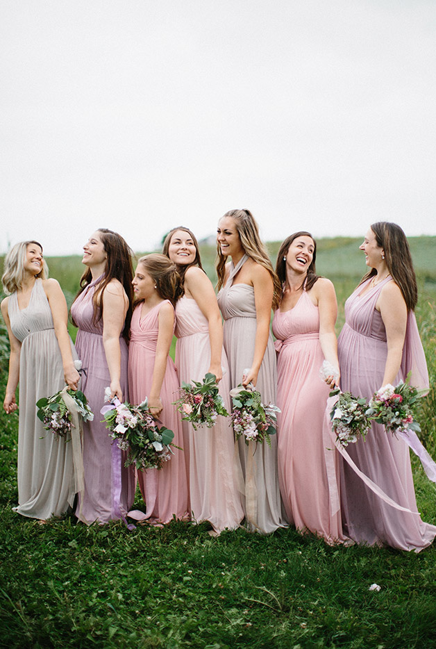 Bridesmaids in pastel colors lined up in green field