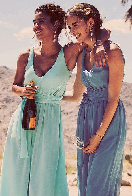 Colorful bridesmaids walking through desert