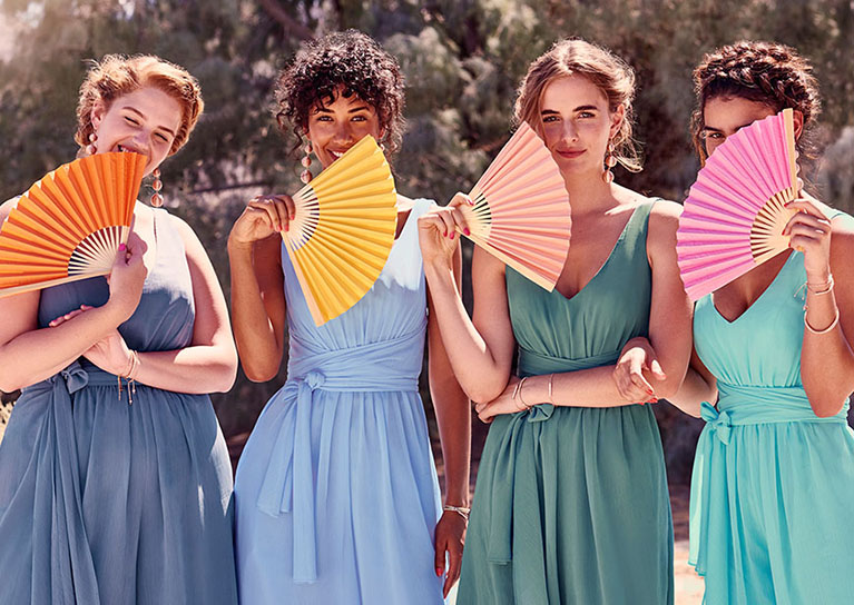 Four bridesmaids holding colorful fans