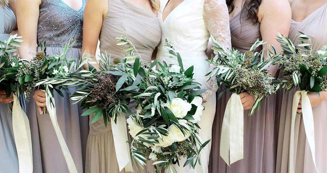 Close up of bride with bridesmaids bouquets