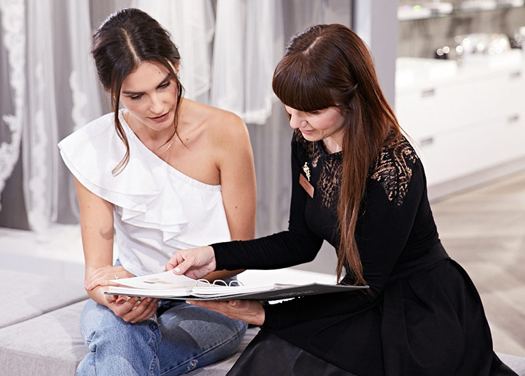 Bridal consultant helping bride-to-be in store