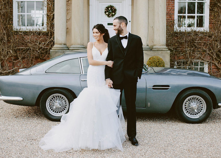 Bride and groom standing in front of luxury car
