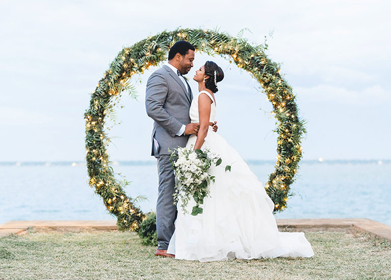 Bride and groom embracing in front of the water and flowers