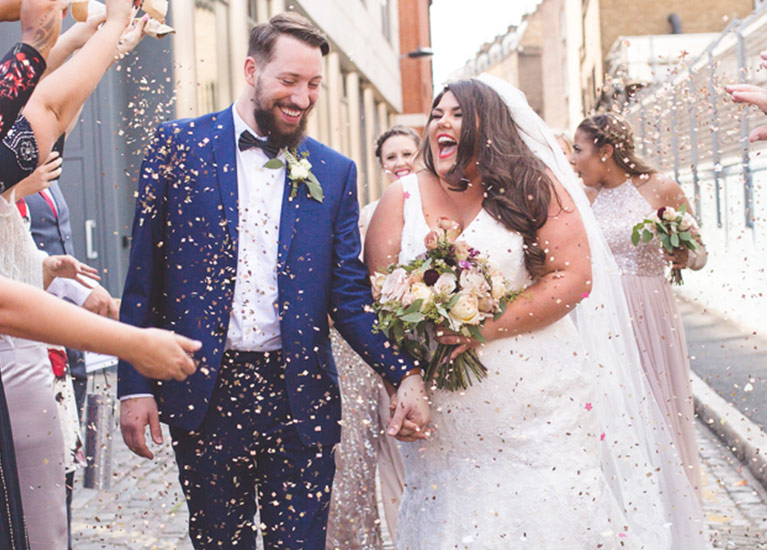 Laughing bride and groom with guests throwing confetti