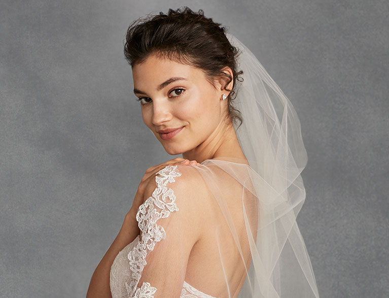 Bride wearing a veil and looking over her shoulder