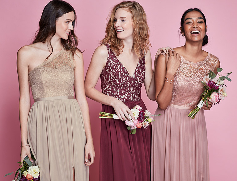 Three bridesmaids in pink dresses smiling and laughing on pink background
