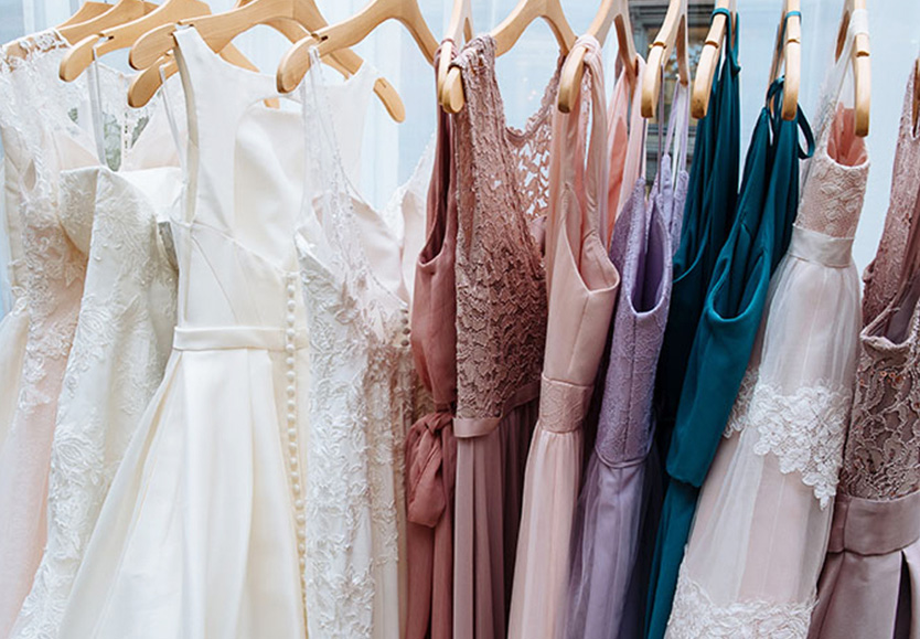 Wedding dresses and bridesmaid dresses in a variety of fabrics on hangers