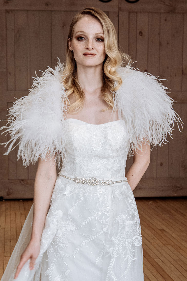 Bride posing with feather outwear jacket