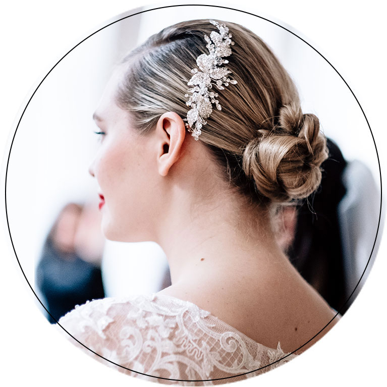 Close up of bride with hair in a put together bun and floral vertical clip