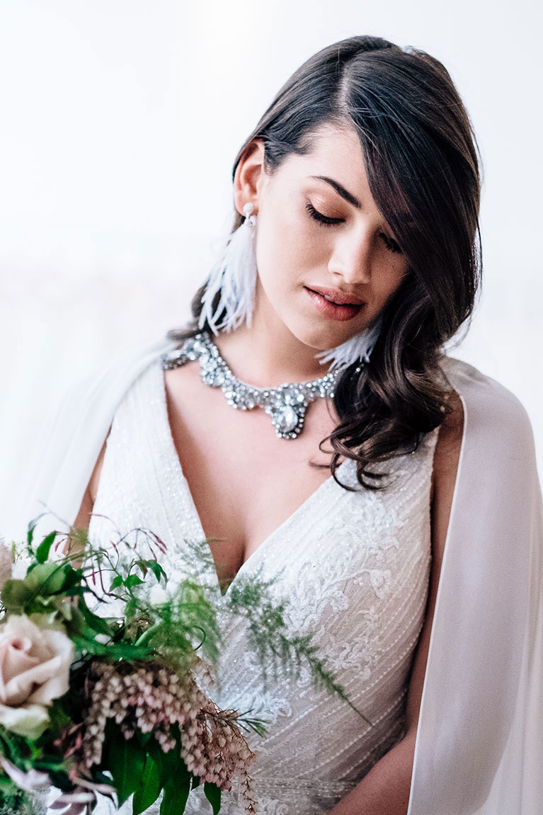 Bride looking down wearing feather earrings and crystal necklace holding a bouquet