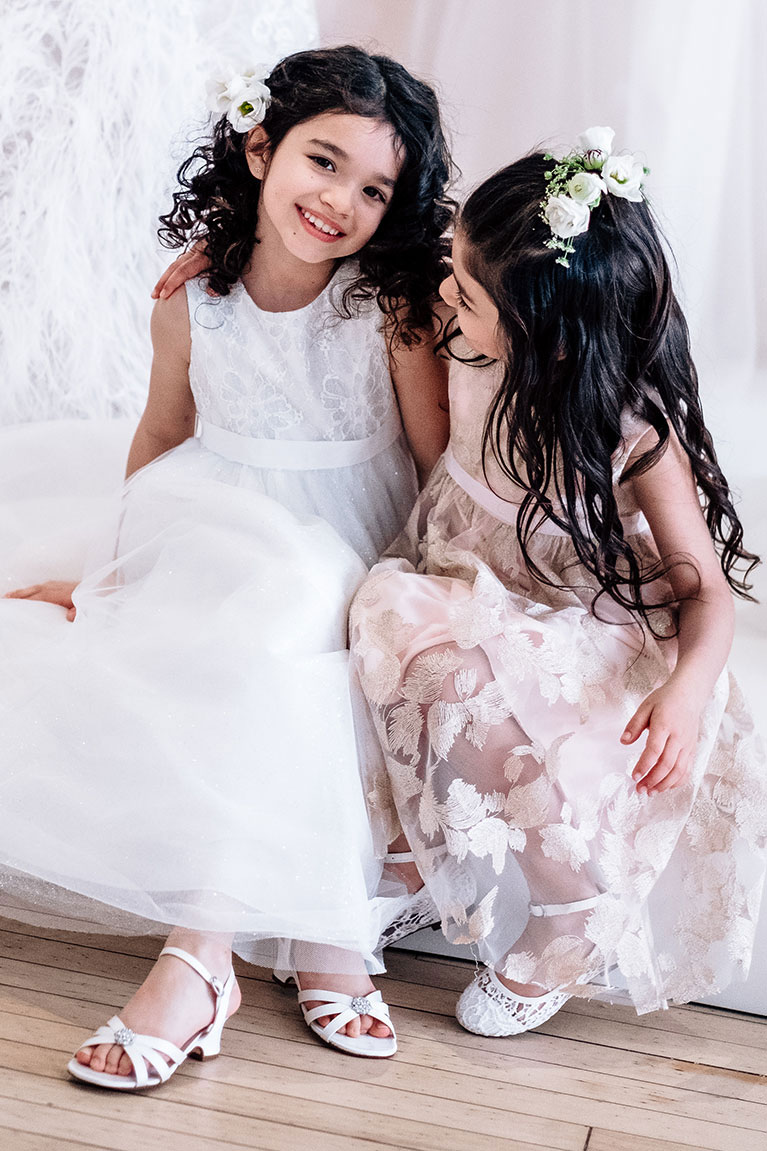 Flower girl smiling at the camera with another little flower girl smiling at her