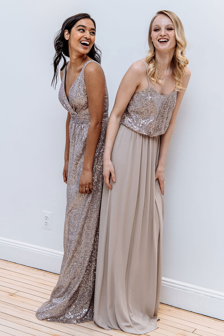 Bridesmaids standing back to back and leaning forward while laughing in sequin dresses