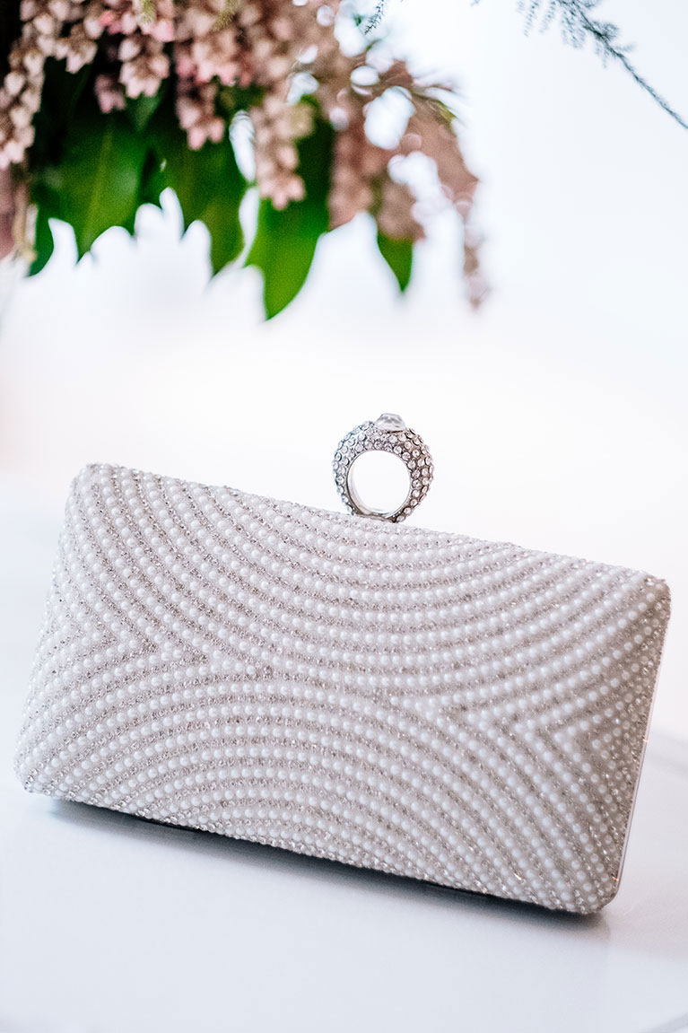 Pearl clutch with handle on white background near pink flowers