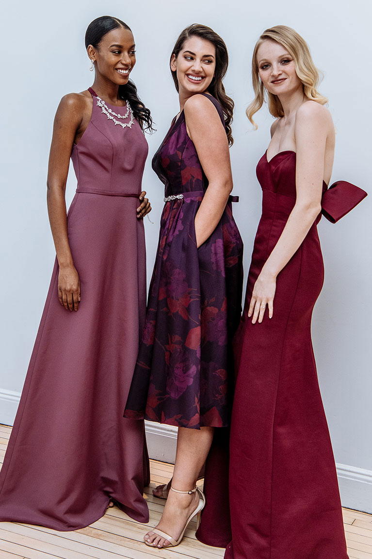 Three bridesmaids wearing different length wine colored dresses