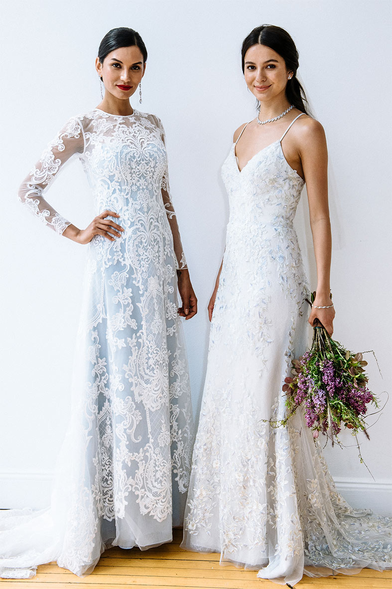 Two brides wearing wedding gowns with blue undertones