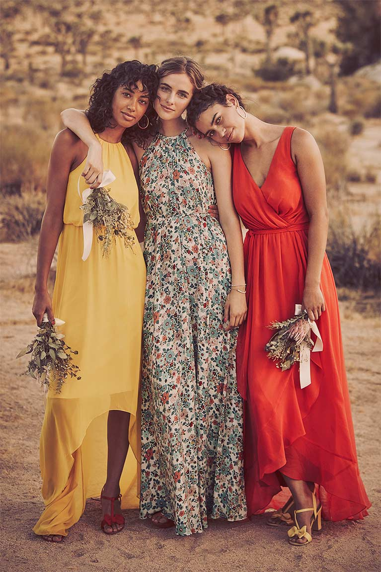 Bridal party in the desert wearing different style dresses, yellow, floral, and red.