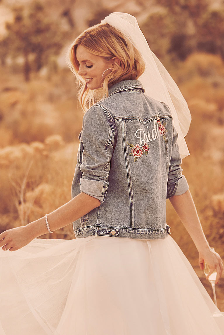 Bride in the desert wearing denim jacket, wedding gown, and veil.