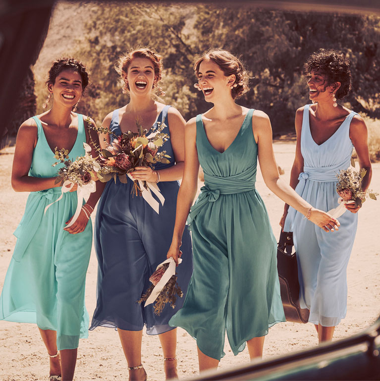 Bridal Party walking together in blue hued dresses.