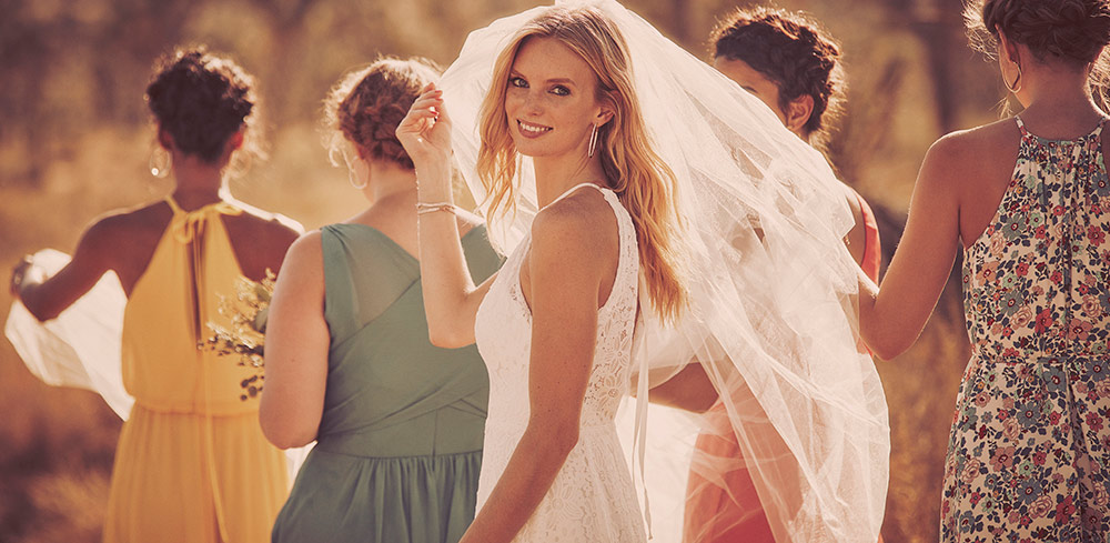 Bride walking in desert in wedding gown and veil, with her bridal party.