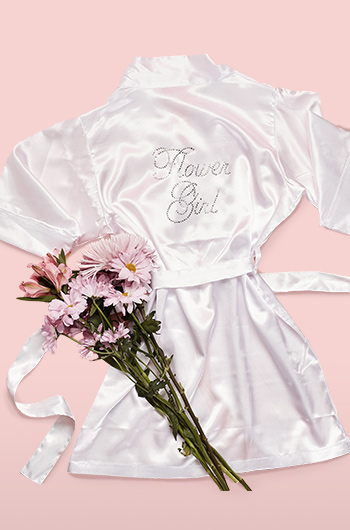 White flower girl robe with pink bouquet of flowers