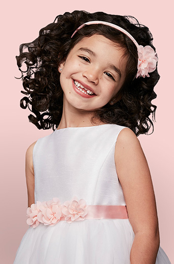 Cute smiling flower girl with pink flower headband and matching belt