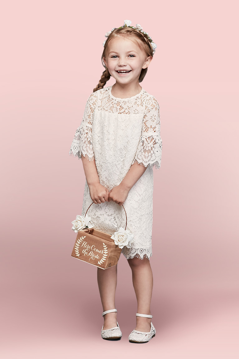Cute flower girl in lace dress holding wooden flower basket