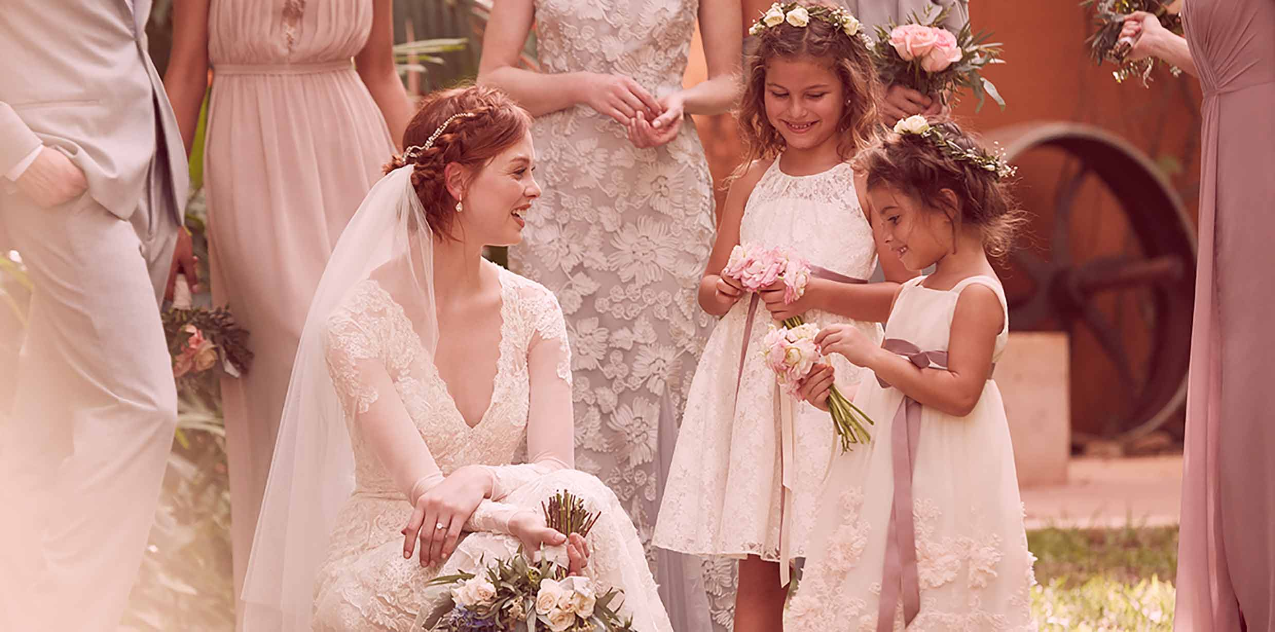 Bride kneeling down and smiling at flower girls