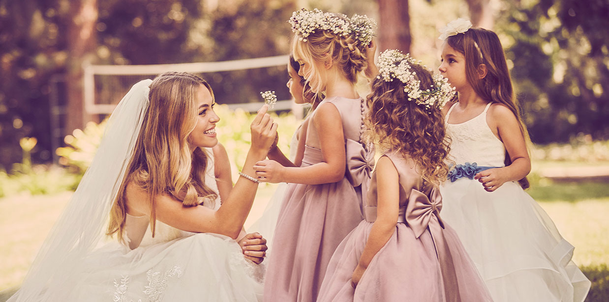 Bride kneeling by flower girls holding babys breath