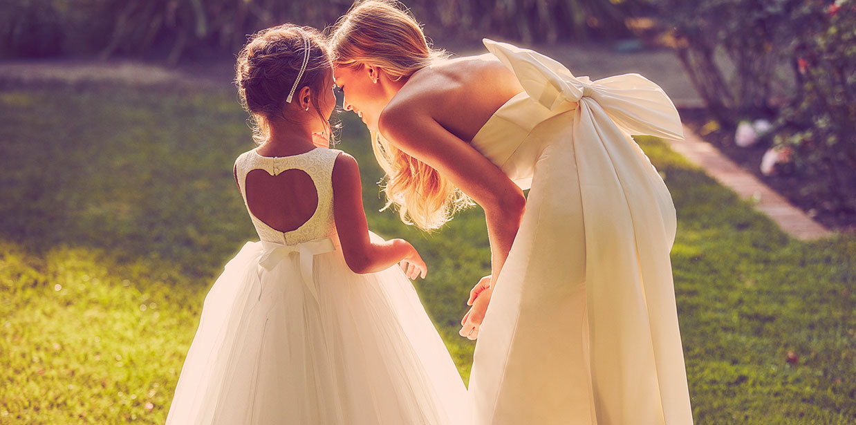 Bride leaning down to flower girl with heart shaped back dress